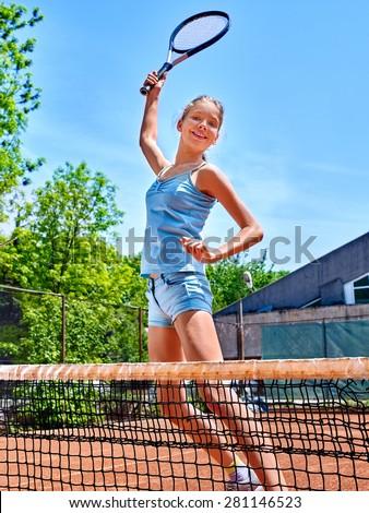 Girl teen sportsman with racket  jump near net on  tennis court.  - stock photo
