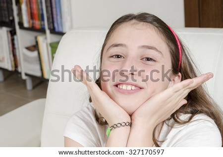 Girl teenage brunette is looking at camera with smile, her hands in her face. - stock photo