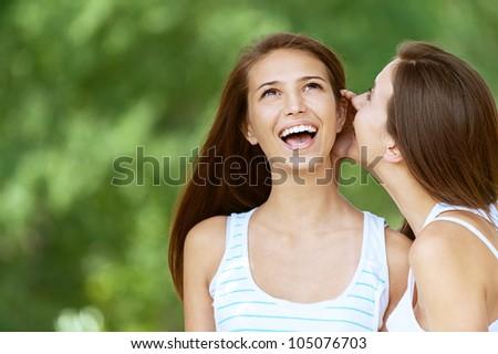 Girl tells her friend gossip, against green of summer park. - stock photo