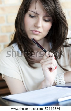Girl thinking and looking at the paper on the desk holding a pen - stock photo