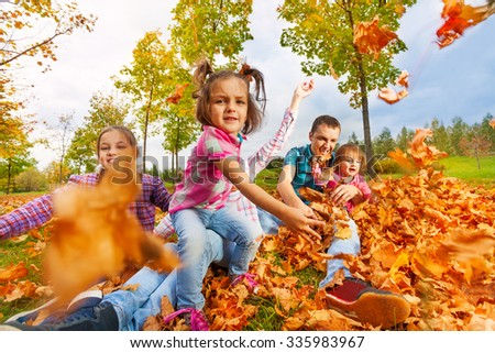 Girl throws autumn maple leaves to camera - stock photo
