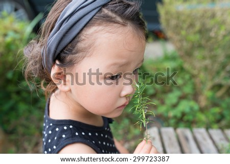 Girl to smell the scent of rosemary - stock photo