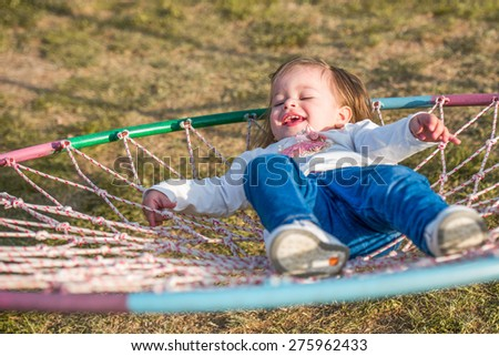 girl toddler laying and laughing in a nest basket swing - stock photo