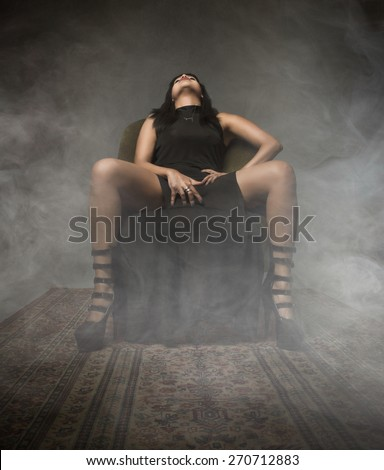 girl touching for pleasure, dark and foggy background - stock photo