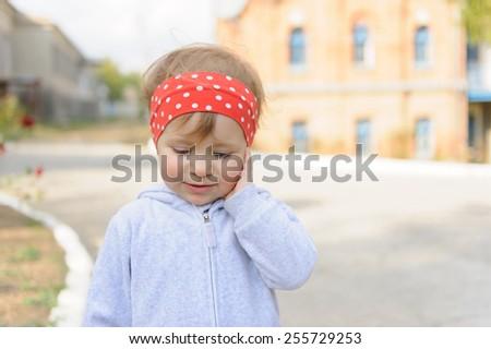 girl touching her cheek in street - stock photo