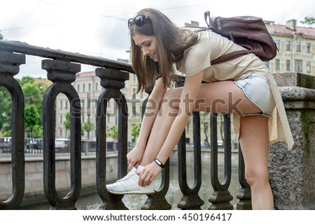 Girl tourist with black fitness bracelet adjusts laces on white sneakers. White girl with long brown hair and sunglasses on her head and a small backpack. On the street, the promenade of the river. - stock photo