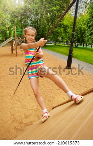 Girl tries to climb on wooden construction - stock photo