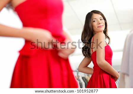 Girl trying dress in looking in mirror cheerful and happy. Cute beautiful mixed race Asian / Caucasian young woman in red dress. - stock photo