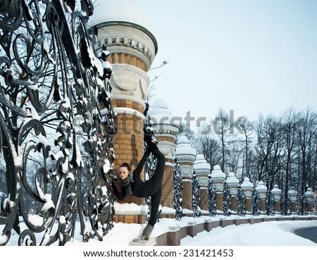 Girl, twice world champion fitness Maria Popretinskaya doing stretching in the winter at the fence of the Mikhailovsky Garden, famous forged lattice Savior, Benoit, artists Kverfeldt, Parland - stock photo