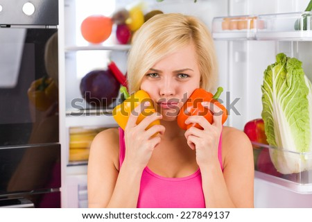 girl unhappy look to red yellow pepper, near refrigerator open door, diet healthy food, young woman sad vitamin vegetables negative emotion - stock photo