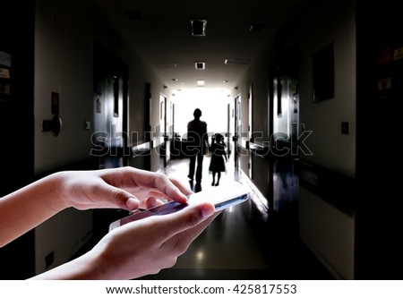 Girl use mobile phone, blur image of a mother and daughter walking on the dark corridor in the hospital as background. - stock photo