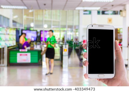 Girl use mobile phone,blur image of check point in building as background. - stock photo