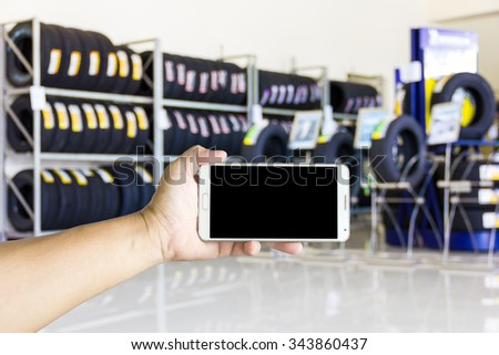 Girl use smart phone, blur image of shop and tire repair services as background. - stock photo