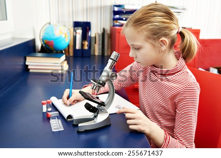 Girl uses a microscope and writes results at home learning table - stock photo