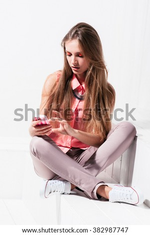 Girl uses new features of her phone - stock photo