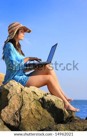 girl using a laptop near the sea - stock photo