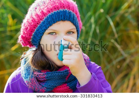 Girl Using Inhaler on a autumn day - to Treat Asthma Attack. Inhalation treatment of respiratory diseases. Shallow depth of field. Allergy concept. Asthma child.  - stock photo