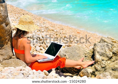 girl using laptop by the sea - stock photo
