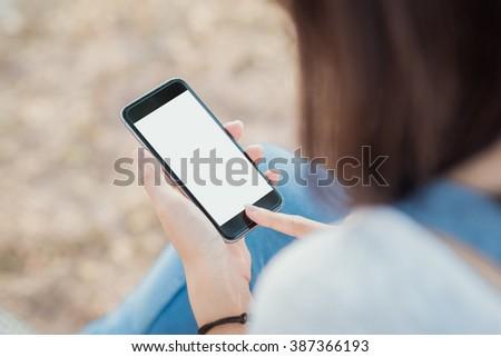 girl using smartphone outdoors. girl using smartphone in park.  woman using smartphone white screen. girl hand holding smartphone. - stock photo