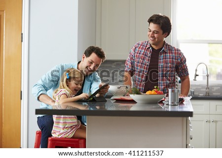 Girl using tablet computer in kitchen with her male parents - stock photo