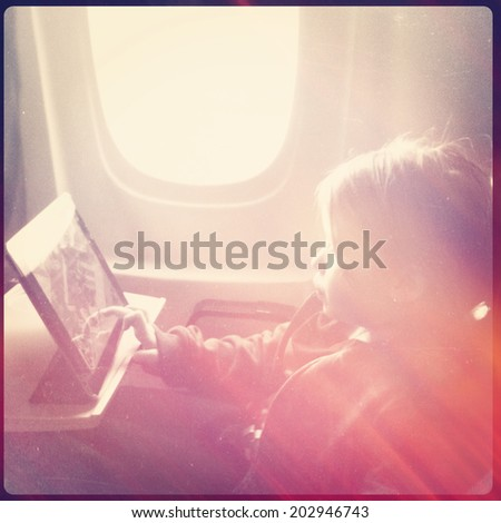 Girl using tablet on Airplane - Instagram effect - stock photo