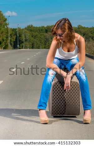 girl waiting for of associated car on the road - stock photo