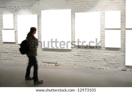 Girl walk through frames on a brick wall - stock photo
