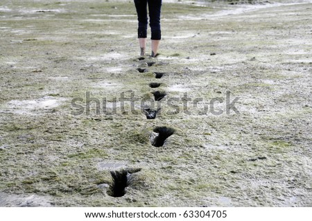 Girl walking barefoot trough mudflat in Brittany, France - stock photo