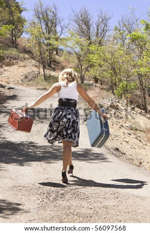 Girl walking down road carrying suitcases. - stock photo