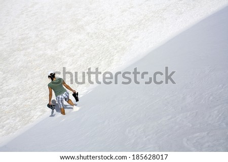 Girl walking down the dune in White Sand Dunes National Park in New Mexico. - stock photo