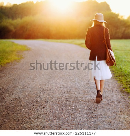 girl walking down the road among fields in sunset light. Back to camera. Outside. - stock photo