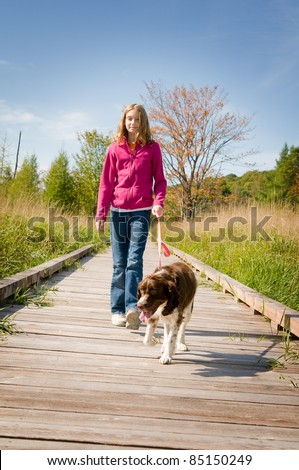 girl walking her dog on a boardwalk - stock photo