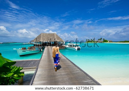 girl walking on the footbridge leading to the jetty on maldives island resort. - stock photo