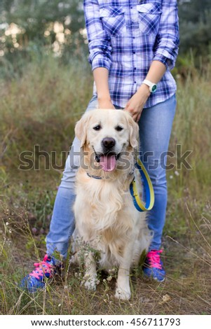 Girl walking with a dog on a green meadow - stock photo