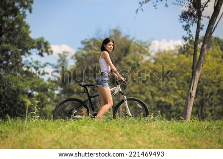 girl walking with bike on mountain grass - stock photo