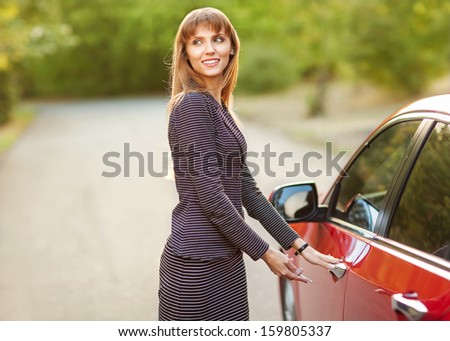 girl want open door of red car outside - stock photo