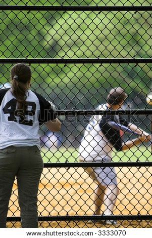 Girl watching and supporting a team mate play baseball - stock photo