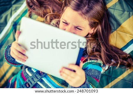 Girl Watching Movie on Her New Tablet While Laying in the City Park. - stock photo