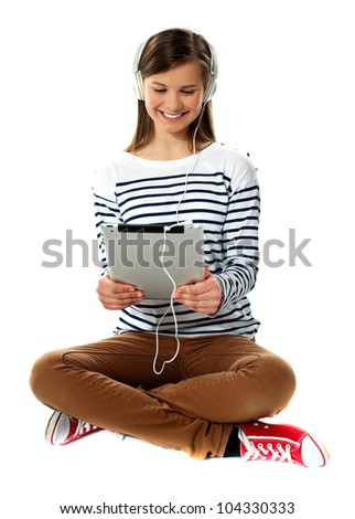 Girl watching video on tablet pc with headphones attached to it - stock photo