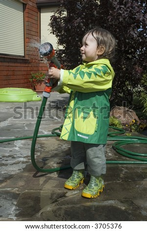 girl watering the garden. water fight - stock photo