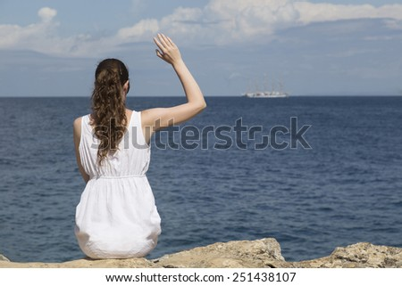Girl waving to the sailboat - stock photo