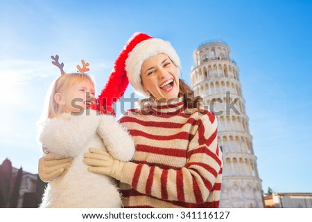 Girl wearing funny reindeer antlers pulling Christmas hat from head of her smiling mother in front of Leaning Tour of Pisa, Italy. They spending exciting Christmas time traveling. - stock photo