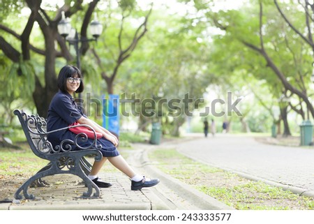 Girl wearing glasses sitting on the bench. Relax under large tree And along corridor within the park. - stock photo