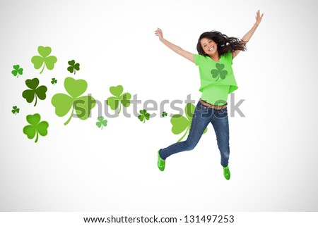 Girl wearing green shamrock t-shirt jumping for joy on shamrock background - stock photo