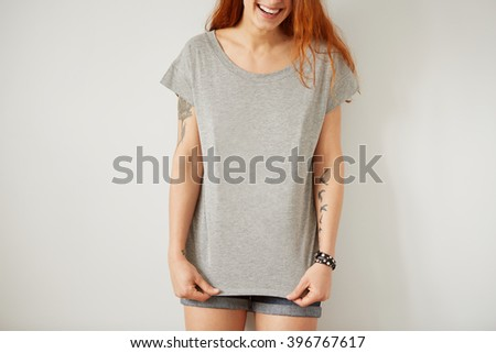 Girl wearing grey blank t-shirt standing on the background of a white wall.  - stock photo