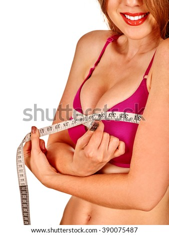 Girl wearing in lingerie measures her breast measuring tape. Health female breast. - stock photo