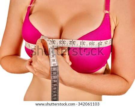 Girl wearing in red lingerie measures her breast measuring tape. Isolated. - stock photo