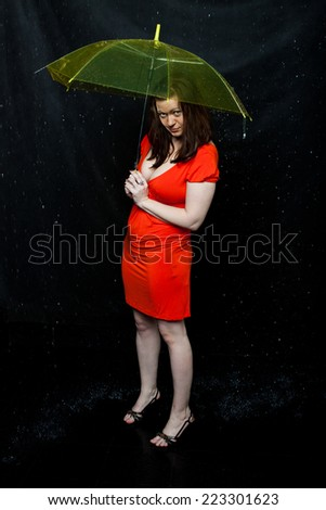 girl wearing red dress stands under an umbrella - stock photo