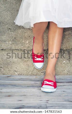 Girl wearing red sneakers leaning on the wall - stock photo