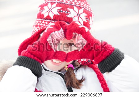 Girl wearing red winter hat and mittens doing a heart with her hands - stock photo